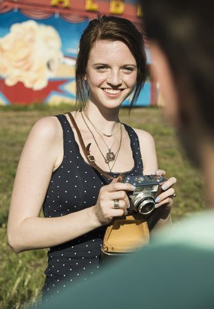 Young couple taking photographs on SLR camera at funfair