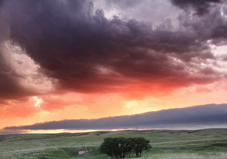ongoing: Roll cloud hangs low in the distance with sunset colors reflecting ongoing storm convection, Lexington, Nebraska, USA