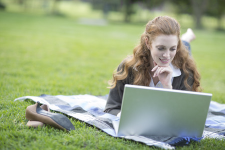 technology: Young woman reclining on picnic blanket using laptop in park LANG_EVOIMAGES
