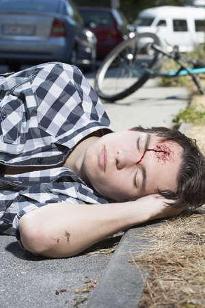 hemorragias: Young man lying on roadside with bleeding forehead LANG_EVOIMAGES