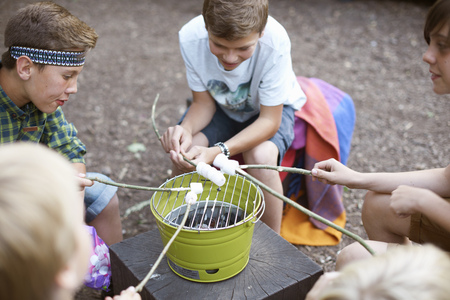 Group of young boys toasting marshmallows over bucket barbecue LANG_EVOIMAGES