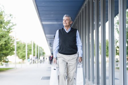 go shopping: Senior adult businessman walking with shopping bags