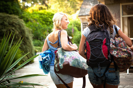 Rear view of two female friends out walking with backpack and bags