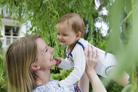 Mother holding up baby daughter face to face in garden
