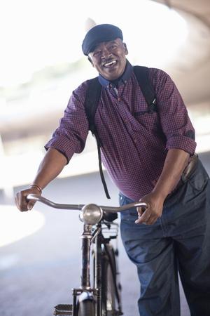 Senior man pushing bicycle through city underpass LANG_EVOIMAGES