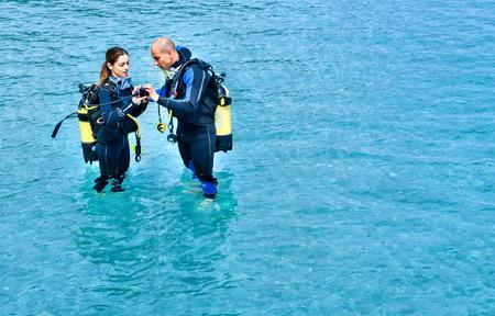 Couple preparing to scuba dive in sea, La Maddalena, Sardinia, Italy