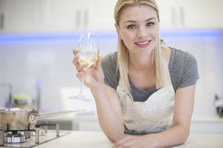 Portrait of young woman drinking glass of white wine in kitchen