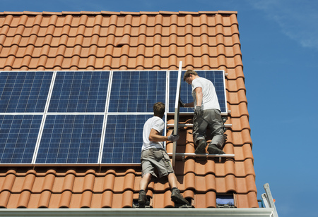 Workers installing solar panels on roof framework of new home, Netherlands