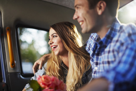 Young woman with boyfriend and bunch of roses in city taxi LANG_EVOIMAGES