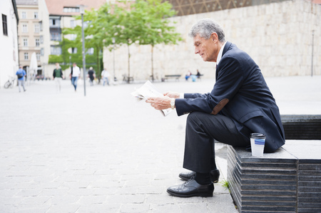 Senior businessman sitting in city plaza reading newspaper