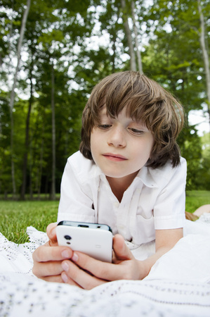 7 8: Boy lying on front reading messages on smartphone