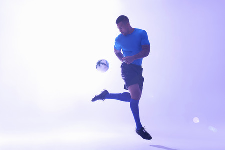 Studio shot of young male soccer player keeping ball mid air with back kick LANG_EVOIMAGES