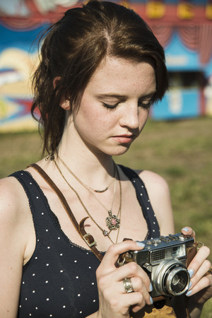 vintage: Young woman photographing on SLR camera at funfair LANG_EVOIMAGES