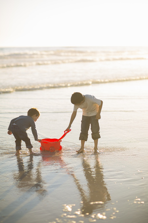 leaning on the truck: Brothers filling toy truck with seawater on beach