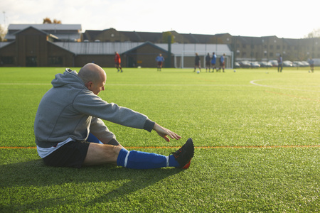 50 54 years: Football player stretching before game