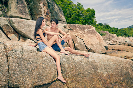 Young couple sitting together on rocks