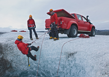 54: Ice climbers on glacier using the 4X4 as a belay anchor to lower off into the icecave, Breidamerkurjokull, East Iceland, Iceland