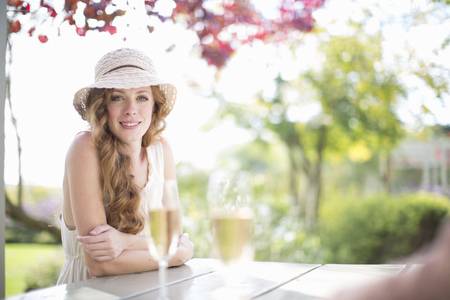 Portrait of beautiful young woman at table in garden restaurant LANG_EVOIMAGES