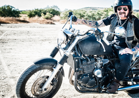 one mature man only: Portrait of male motorcyclist on arid plain,Cagliari,Sardinia,Italy LANG_EVOIMAGES