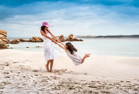 Young woman swinging daughter on beach, La Maddalena, Sardinia, Italy