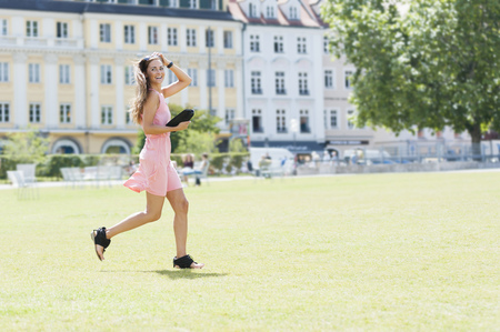 Mid adult woman running across grass, holding clutch bag