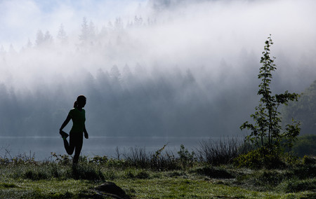 Female runner stretching by misty lake, Capel Curig, Snowdonia, North Wales, UK