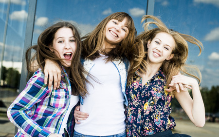 Three young women shaking hair in a row LANG_EVOIMAGES