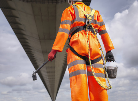 one mature man only: Bridge painter looking at  suspension bridge. The Humber Bridge, UK was built in 1981 and at the time was the worlds largest single-span suspension bridge