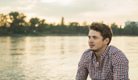 Young man wearing checked shirt by lake LANG_EVOIMAGES