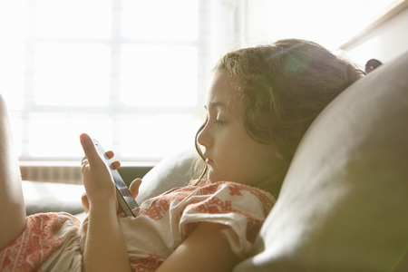 Girl lying on living room sofa browsing smartphone