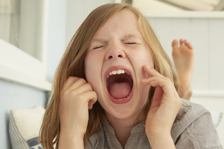 Girl with eyes closed screaming in holiday apartment LANG_EVOIMAGES