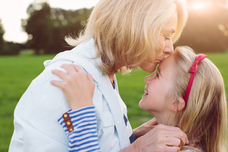 65 69 years: Grandmother kissing granddaughter on forehead