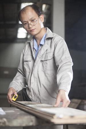 Carpenter measuring wood plank with tape measure in factory, Jiangsu, China LANG_EVOIMAGES