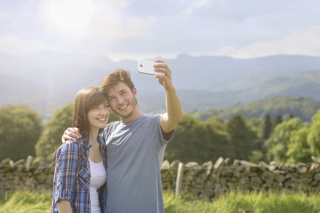 cumbria: Young couple taking self portrait on mobile phone in countryside under sunny sky LANG_EVOIMAGES