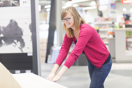 Female customer opening chest of drawers in hardware store