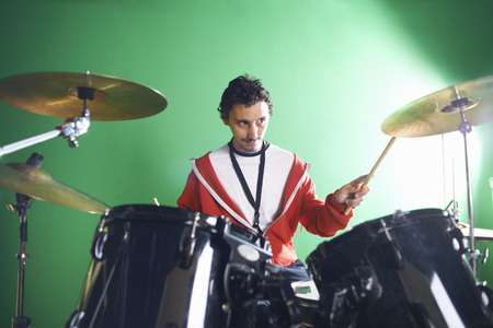 Male student playing drums in college music room LANG_EVOIMAGES