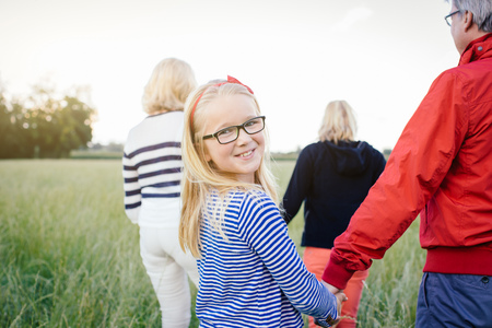 65 69 years: Granddaughter holding grandfathers hand in field