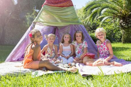 Portrait of five girls in front of teepee