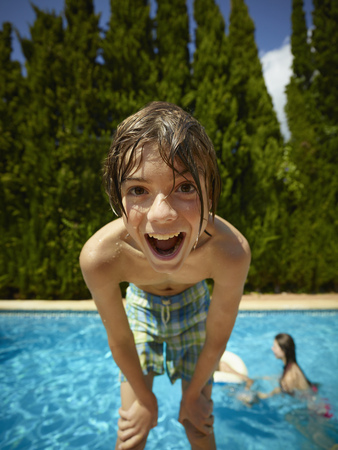 Portrait of boy leaning forward in front of swimming pool, Majorca, Spain
