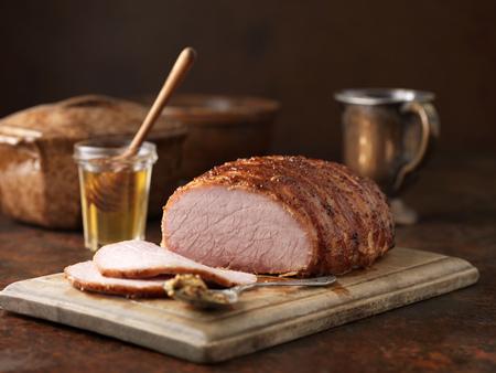 wholegrain mustard: Christmas dinner. Honey and wholegrain mustard gammon on chopping board