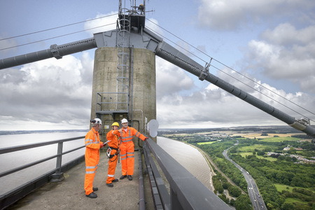 54: Bridge workers on top of suspension bridge. The Humber Bridge, UK was built in 1981 and at the time was the worlds largest single-span suspension bridge LANG_EVOIMAGES