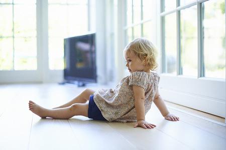 Portrait female toddler sitting on living room floor