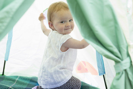 Baby girl playing in tent