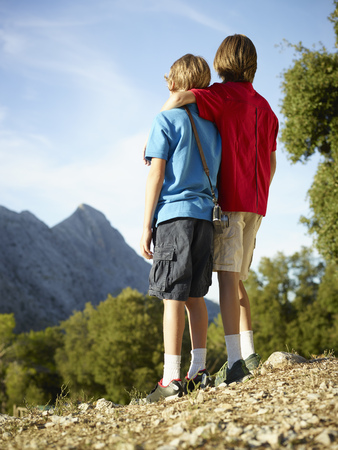 Rear view of two brothers gazing at mountains, Majorca, Spain