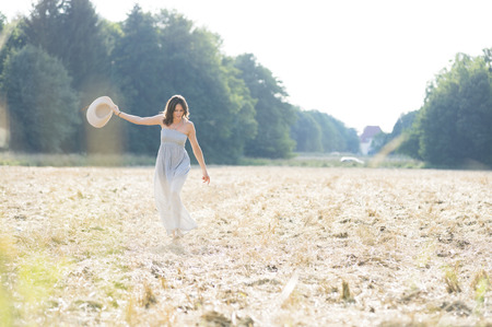 Mid adult woman holding up straw hat strolling in field