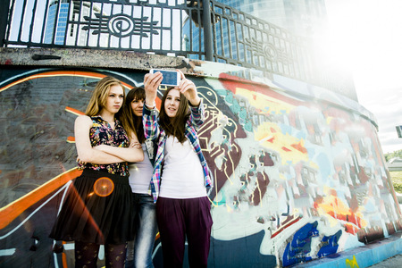 Friends taking selfie,mural in background LANG_EVOIMAGES