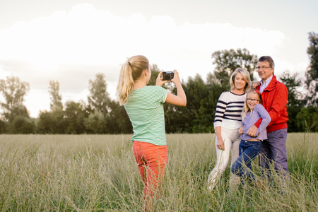 Granddaughter photographing grandparents and sister in field