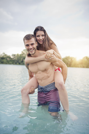 Young man carrying his girlfriend on piggyback in lake