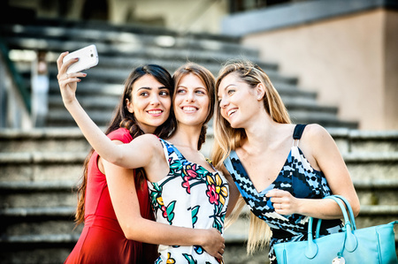 Three fashionable young women taking selfie on stairway, Cagliari, Sardinia, Italy