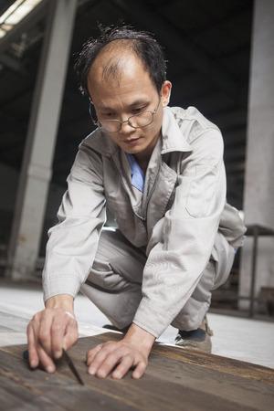 resourceful: Carpenter checking quality of wood plank in factory, Jiangsu, China